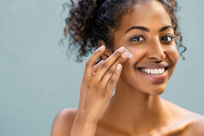 woman applying moisturizing lotion on face